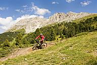 Italy, Dolomites, Mature man biking at latemar mountains - RNF000578