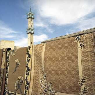 Jordan, Amman, Traditional carpets with minaret in background - PMF000821