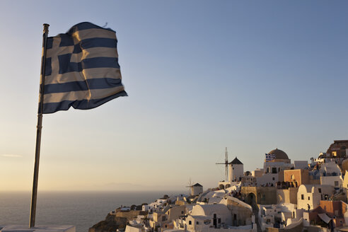 Greece, Cyclades, Thira, Santorini, Greek flag and the town - FOF002790