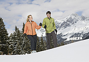 Germany, Bavaria, Young man and woman walking in a snow - WBF000821