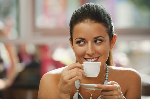 Germany, Munich, Young woman drinking coffee in cafe, smiling, portrait - RNF000511