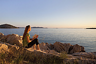 Croatia, Zadar, Young woman with book looking at view from beach - HSIF000099