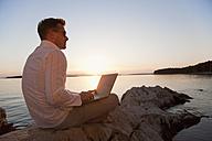 Croatia, Zadar, Young man using laptop on beach - HSIF000101