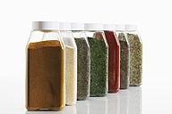 Variety of herbs and spices in glass jar on white background - CSF014484
