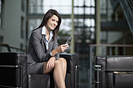 Germany, Bavaria, Business woman with mobile, smiling, portrait - MAEF002694