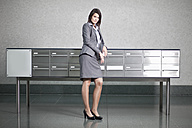 Germany, Bavaria, Business woman standing by table, portrait - MAEF002748