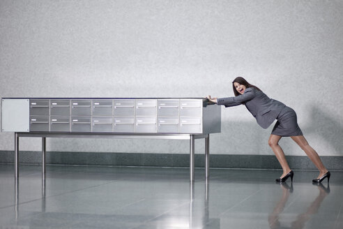 Germany, Bavaria, Business woman pushing table - MAEF002750
