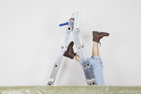 Germany, Cologne, Mature woman fallen down from step ladder during painting living room - GWF001354