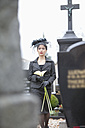 Germany, Bavaria, Young woman with flower at graveyard - MAEF002728