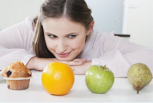 Germany, Cologne, Young woman is confused between fruits and sweets - PDF000144