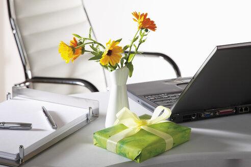 Office scene with flower vase, gift parcel and laptop on desktop - CSF014058