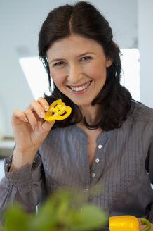 Germany, Munich, Mature woman holding slice of yellow bell pepper, smiling, portrait - NHF001315