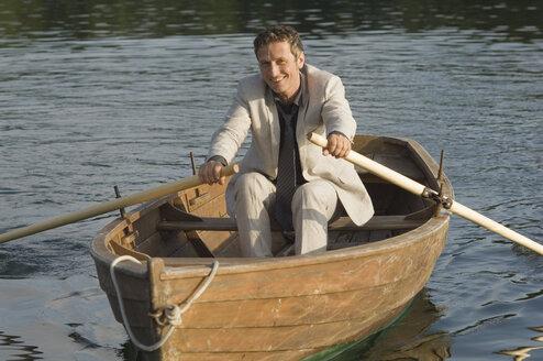 Germany, Bavaria, Wesslinger See, Business man rowing boat in lake after work - CRF002015
