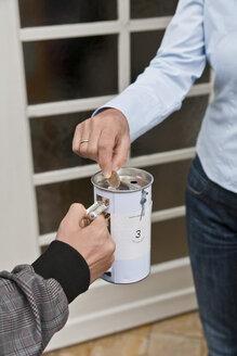 Teenage boy donating money at door - WDF000866