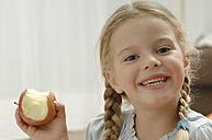 Germany, Bavaria, Girl holding apple, portrait, smiling - CRF002019