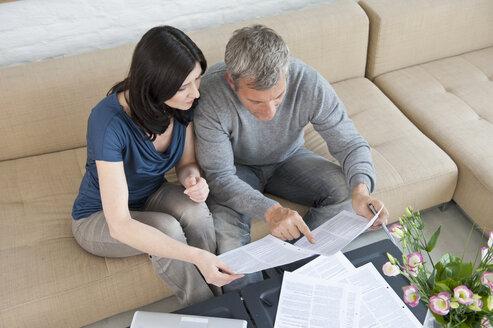 Germany, Munich, Mature couple doing paperwork - NHF001270