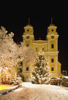 Austria, Salzkammergut, Mondsee, View of church and christmas tree in christmas market at night - WWF001800
