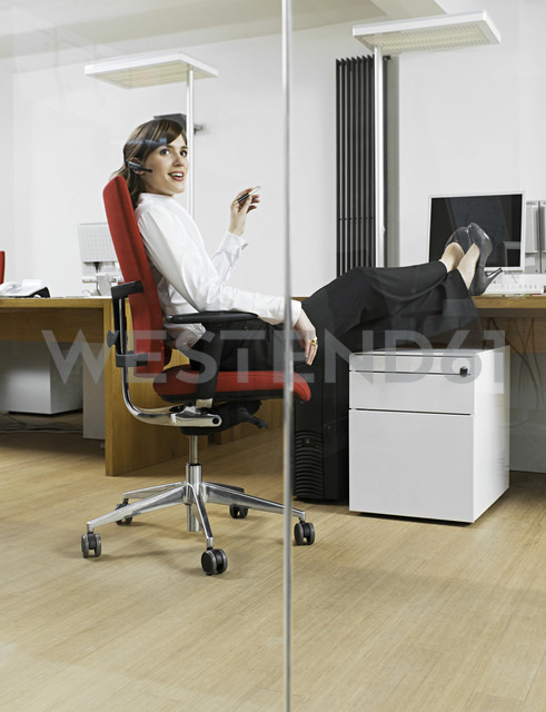 Germany, Cologne, Young woman relaxing in office - WMF000001