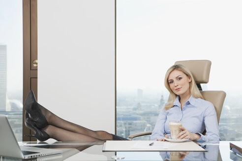 Germany, Frankfurt, Business woman sitting in office with coffee mug - SKF000430