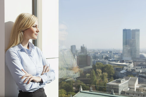 Germany, Frankfurt, Business woman looking through window - SKF000442
