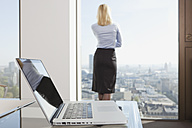 Germany, Frankfurt, Business woman looking through window with laptop in foreground - SKF000445