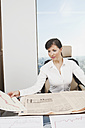 Germany, Frankfurt, Business woman looking at graph and newspaper - SKF000457