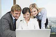 Germany, Frankfurt, Business people using laptop and discussing - SKF000523
