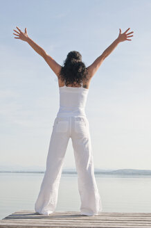 Mid adult woman with arms up standing on jetty - UMF000323