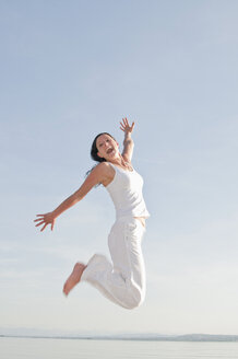 Mid adult woman jumping with mouth open - UMF000324