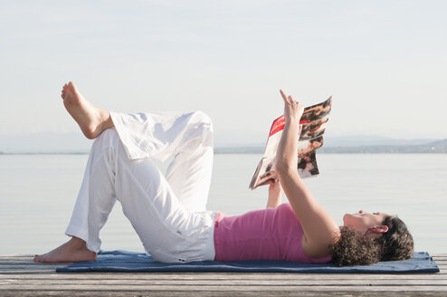 Mid adult woman lying on jetty and reading book - UMF000330