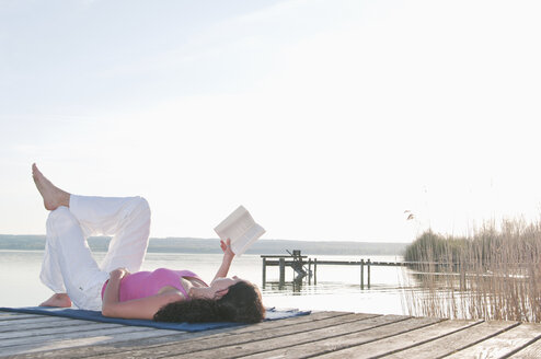 Mid adult woman lying on jetty and reading book - UMF000334