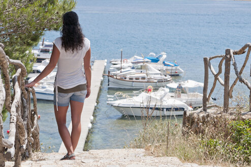 Spain, Balears, Menorca, Mid adult woman looking at boats at jetty - UMF000344