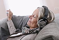 Germany, Wakendorf, Senior woman listening music - WESTF016204