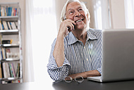 Germany, Wakendorf, Senior man on the phone with laptop, smiling - WESTF016210