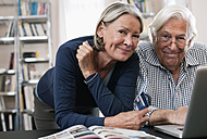 Germany, Wakendorf, Senior  woman with credit card and man using laptop - WESTF016246