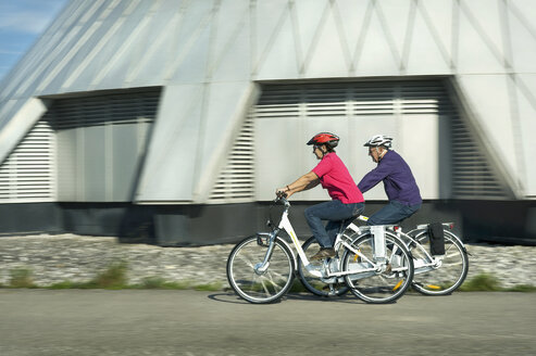 Germany, Bavaria, Raisting, Senior couple riding electric bicycle near radio station - RNF000658