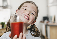 Germany, Cologne, Girl holding a glass of tomato juice - WESTF016294