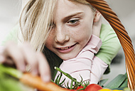 Germany, Cologne, Girl looking at vegetable, close up - WESTF016312