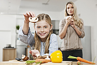 Germany, Cologne, Daughter cutting vegetable with mother in background - WESTF016318