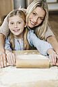 Germany, Cologne, Mother and daughter rolling dough, smiling, portrait - WESTF016321