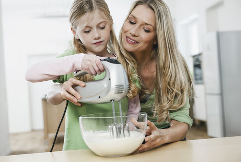 Germany, Cologne, Mother and daughter with electric whisk mixing batter - WESTF016324
