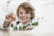 Germany, Cologne, Boy holding egg, smiling, portrait - WESTF016333