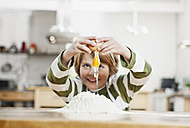 Germany, Cologne, Boy breaking egg on flour - WESTF016336