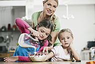 Germany, Cologne, Mother and children preparing muesli for breakfast - WESTF016363