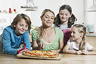 Germany, Cologne, Mother and children looking at pizza and smiling - WESTF016369