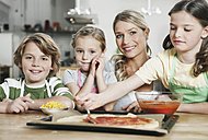 Germany, Cologne, Mother and children in kitchen making pizza - WESTF016372