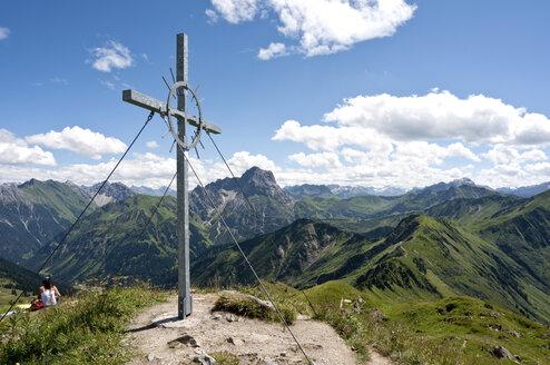 Austria, Vorarlberg, Allgaeu Alps, Cross on mountain, woman sitting in background - UMF000316