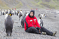 South Atlantic Ocean, United Kingdom, British Overseas Territories, South Georgia, St. Andrews Bay, Mature man sitting with king penguins - FOF003140