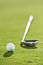 Italy, Kastelruth, Golf ball and golf club on golf course - WESTF016391