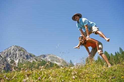 Austria, Salzburg Country, Altenmarkt-Zauchensee, Couple with leapfrog on mountains of Niedere Tauern - HHF003579